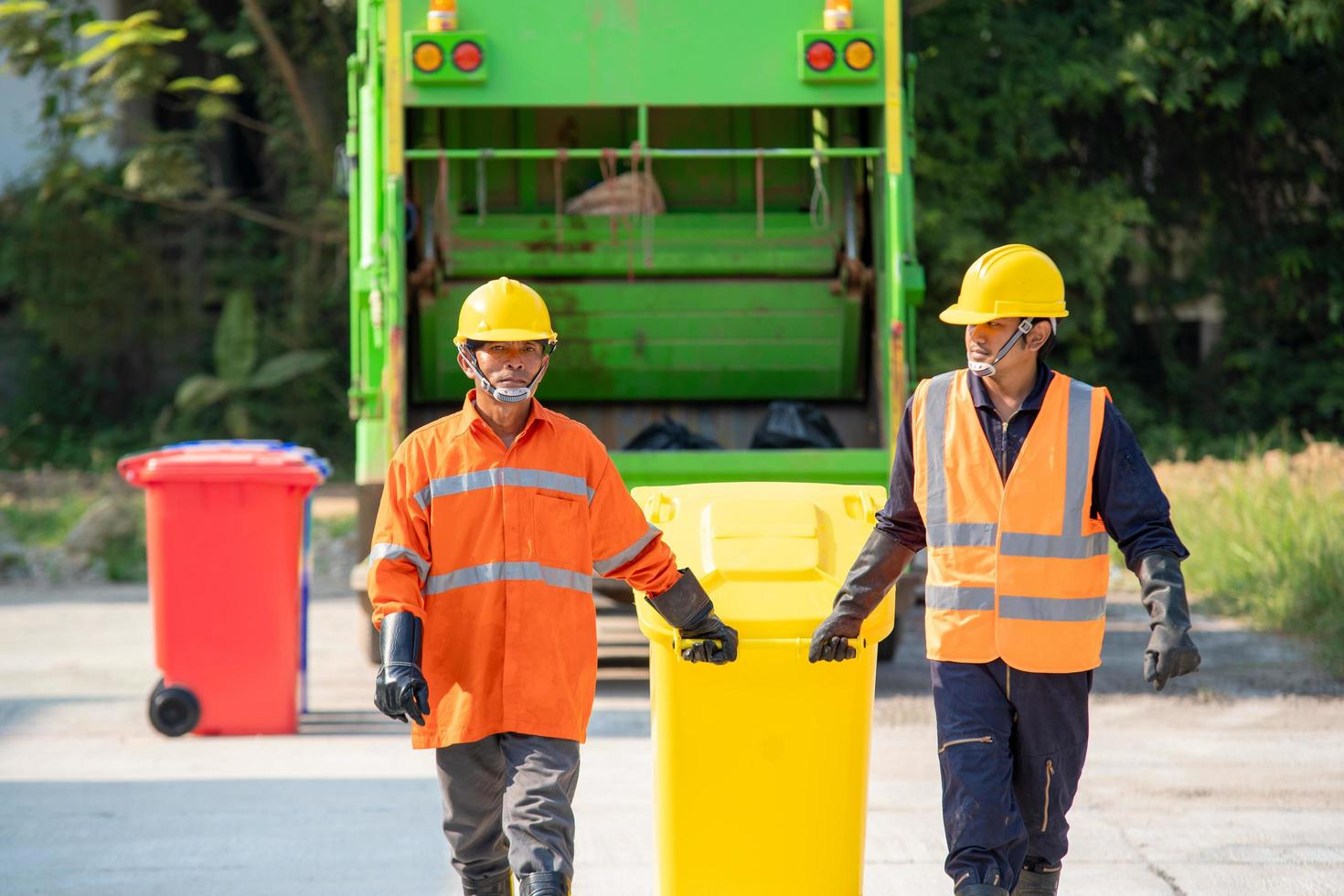 Garbage collectors with bins and truck photo