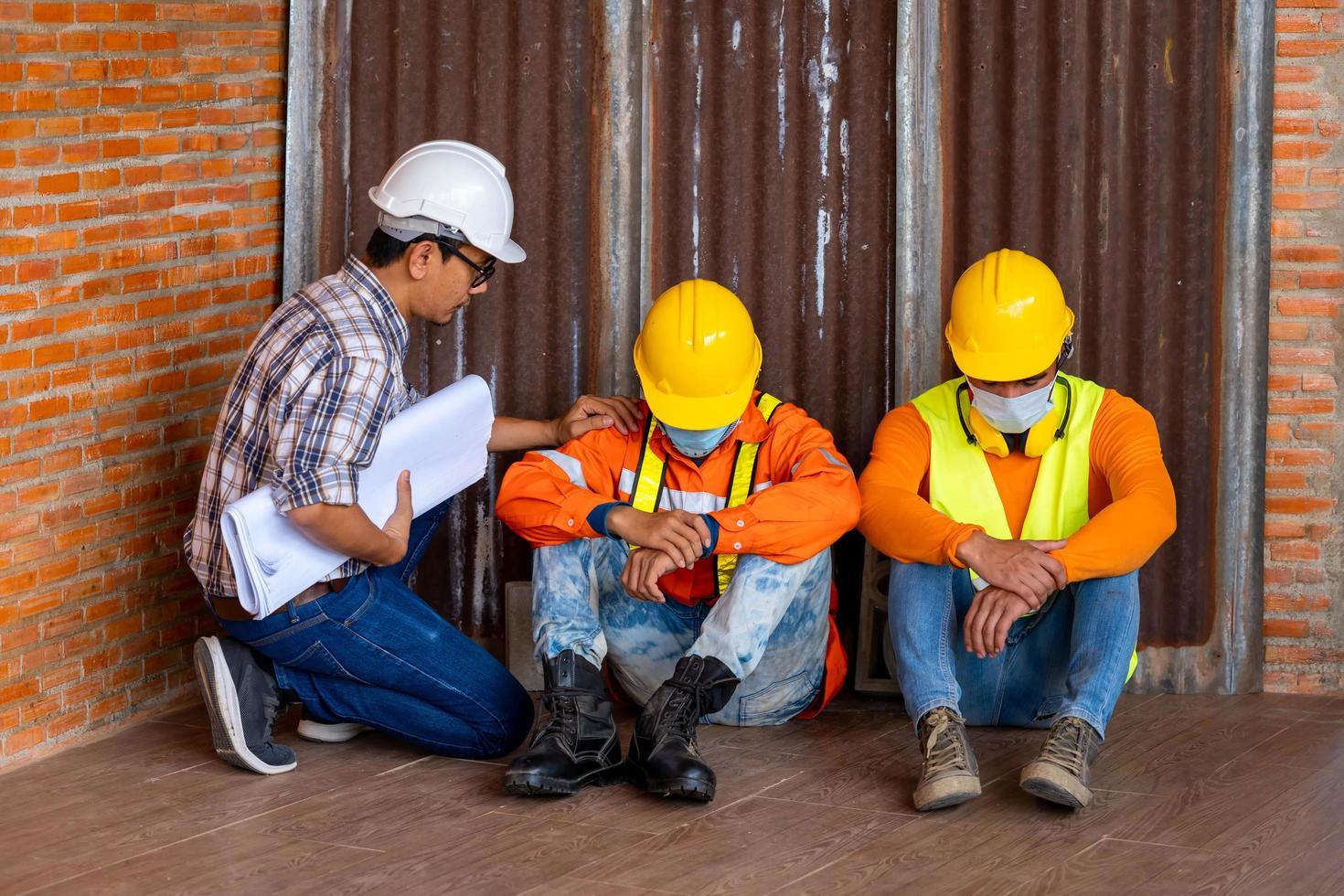 Three men wearing protective equipment next to brick wall photo