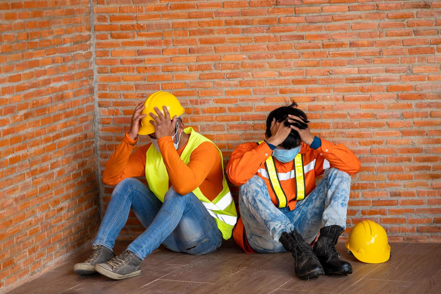 Two men wearing protective equipment next to brick wall photo