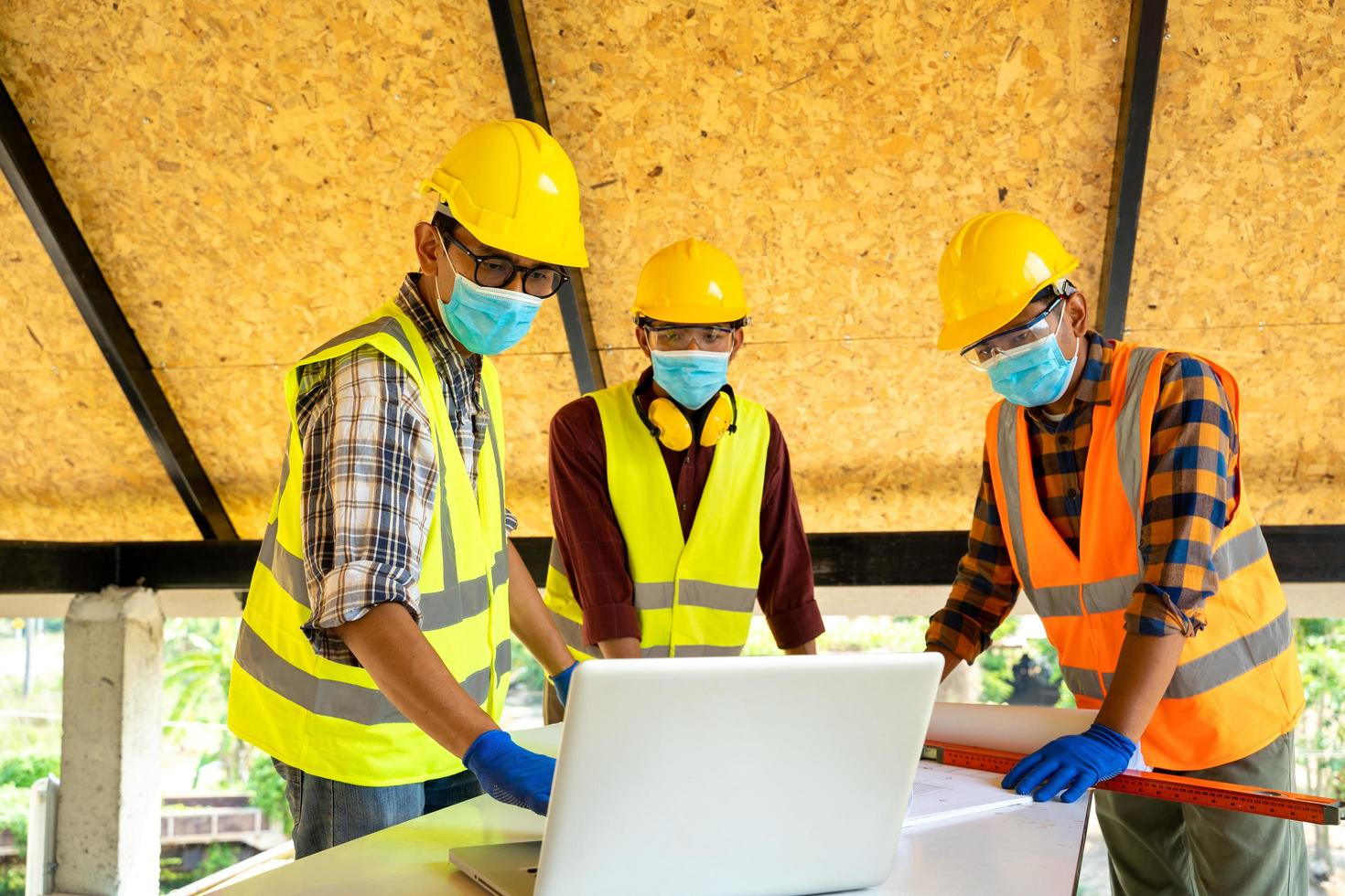 Men wearing protective face masks with laptop photo