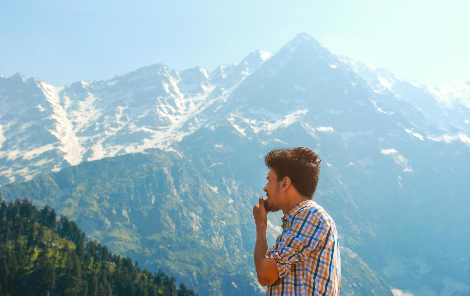 Man in plaid looking at mountains and trees photo