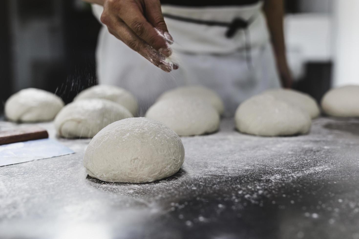 Chef sprinkling flour on dough photo