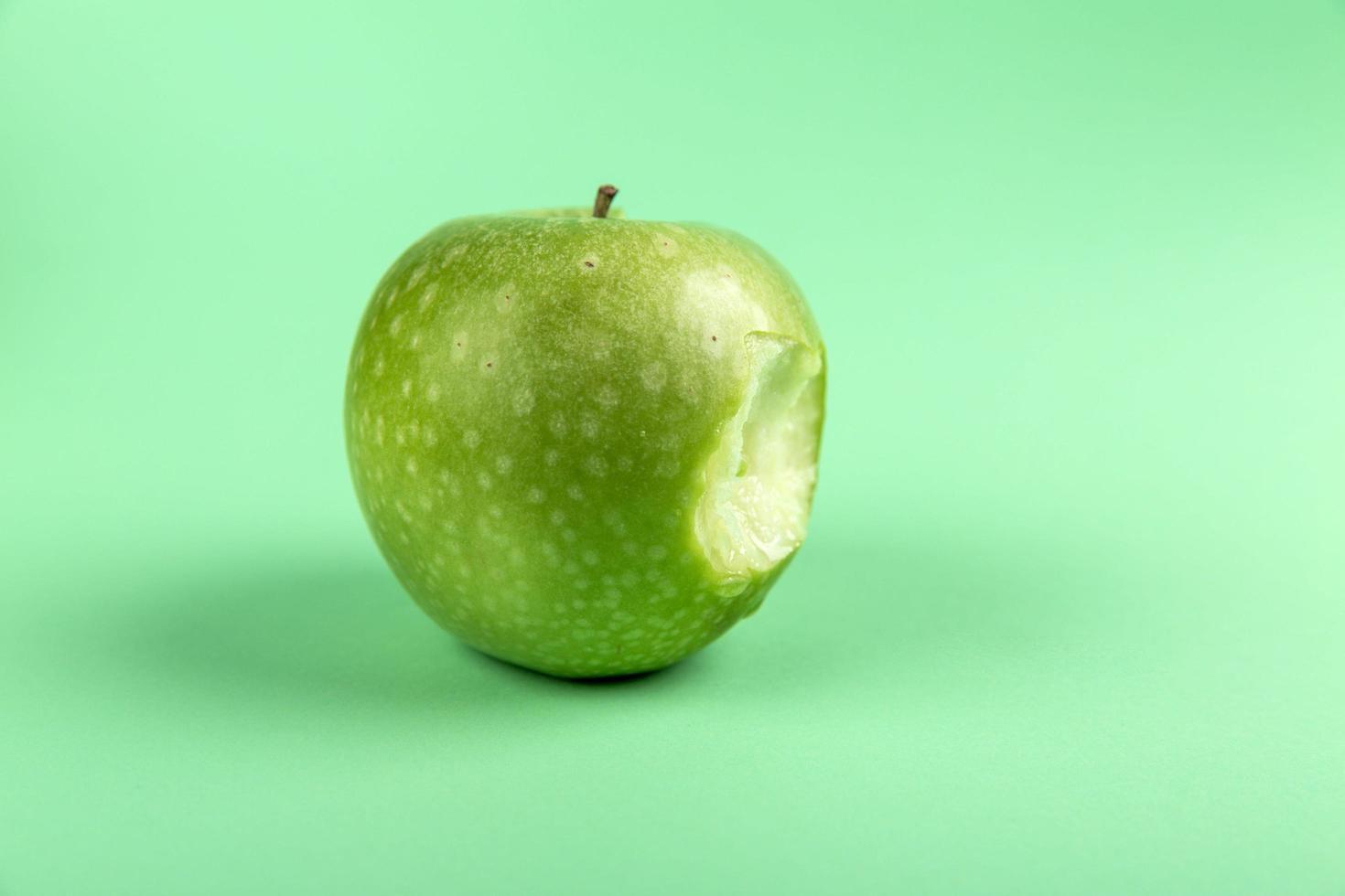 Granny smith apple with bite photo