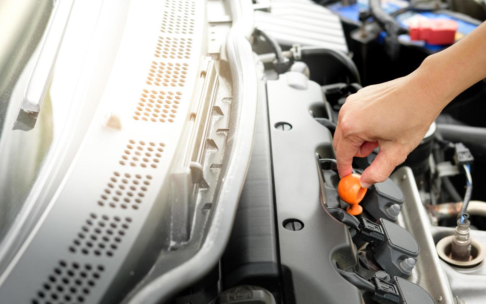 Hand checking car engine photo
