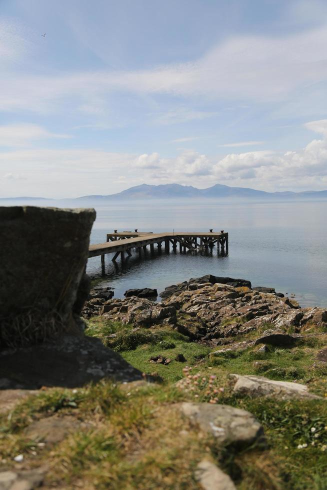 Grass, beach, dock, water, and mountains photo