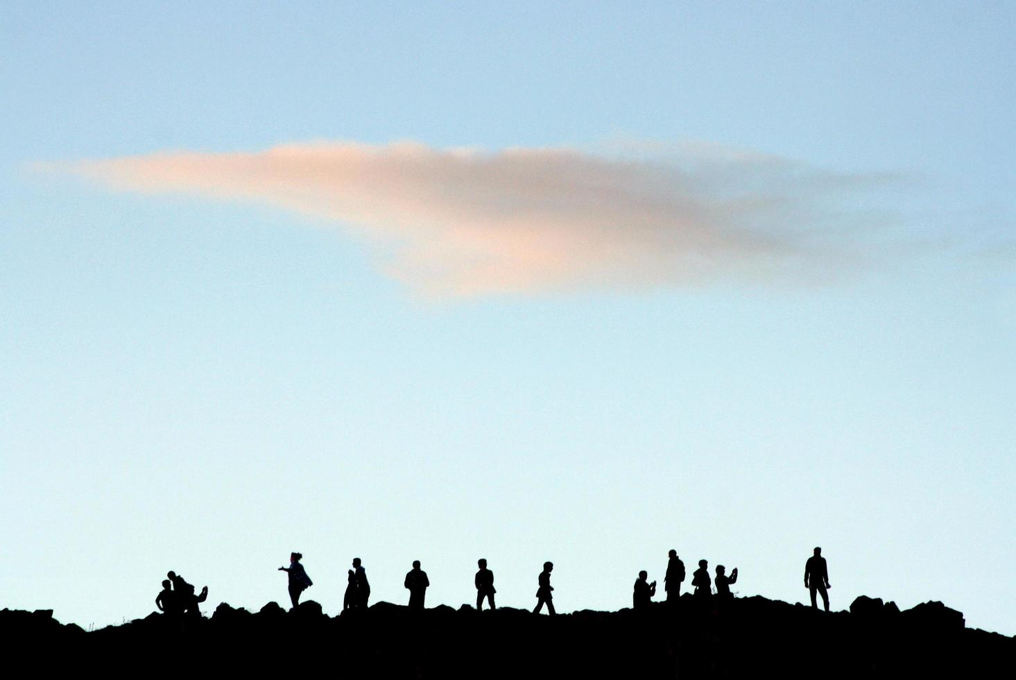 Silhouettes of people on top of a hill photo