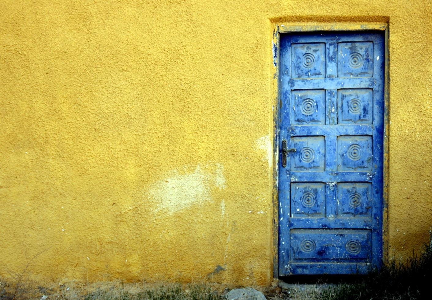 Blue door on a yellow wall photo