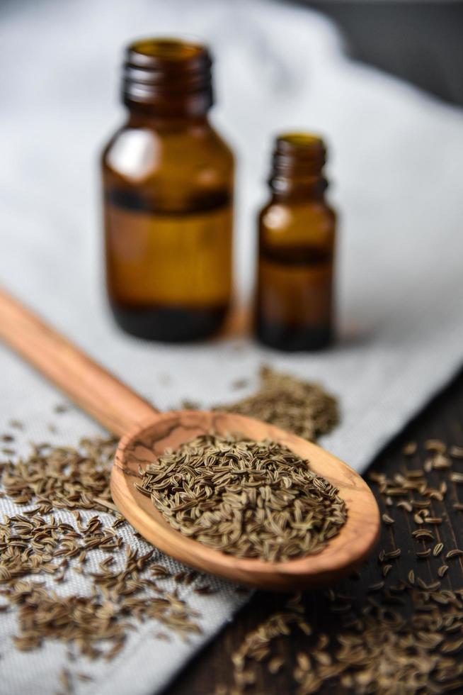 semillas de comino y aceite en botellas foto