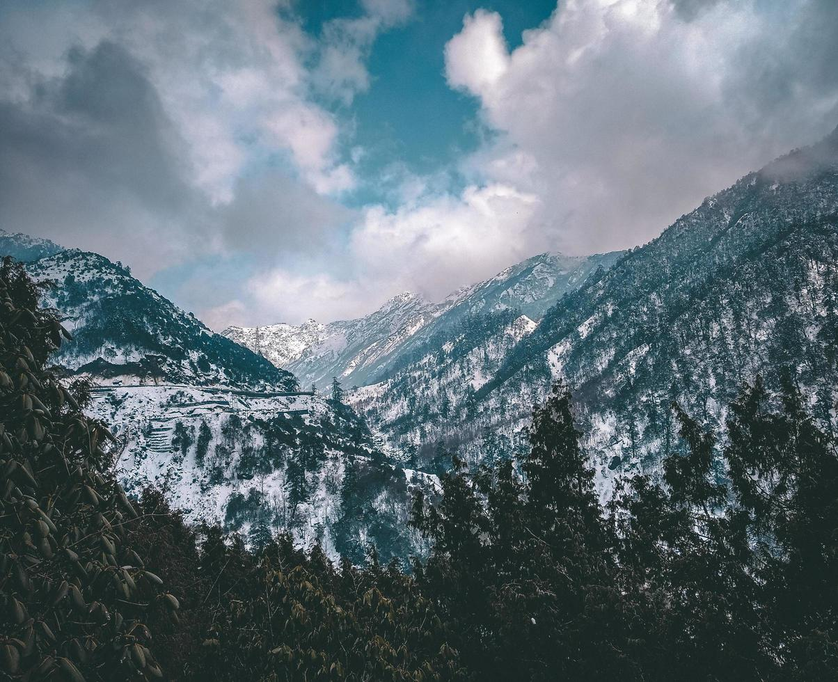 Blue snowy mountains under cloudy sky photo