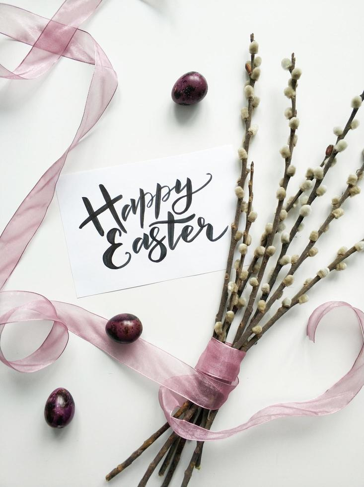 Willow bouquet with Easter sign on white surface photo