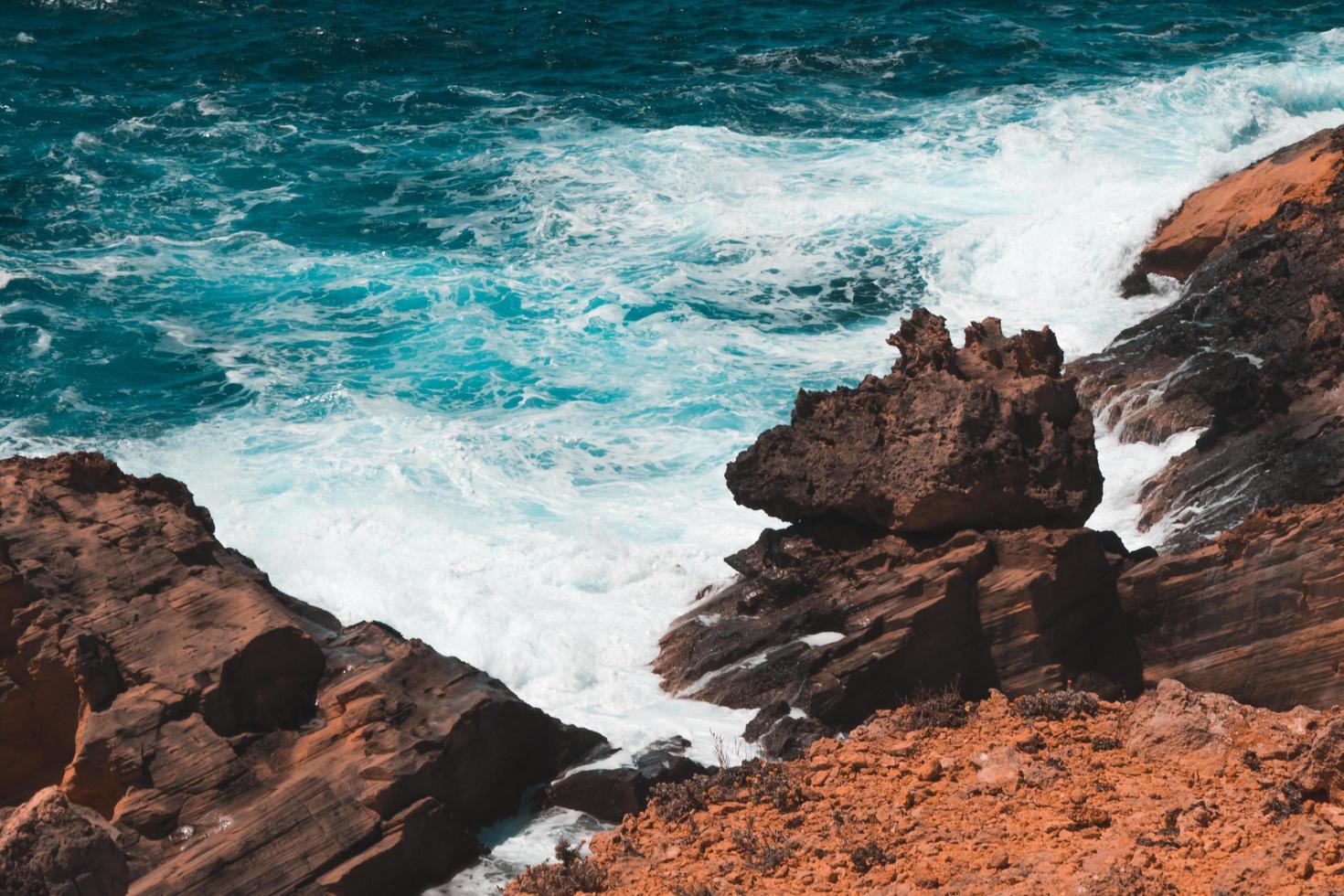 Waves crashing into rocky seashore photo