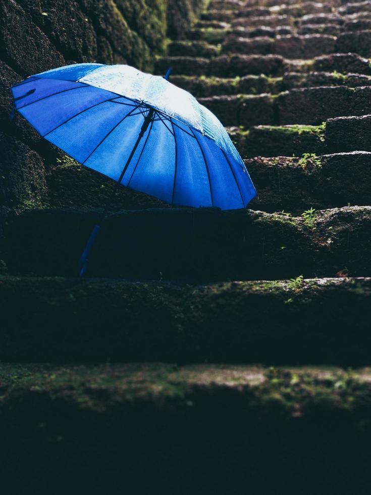 Blue umbrella on black stairs photo