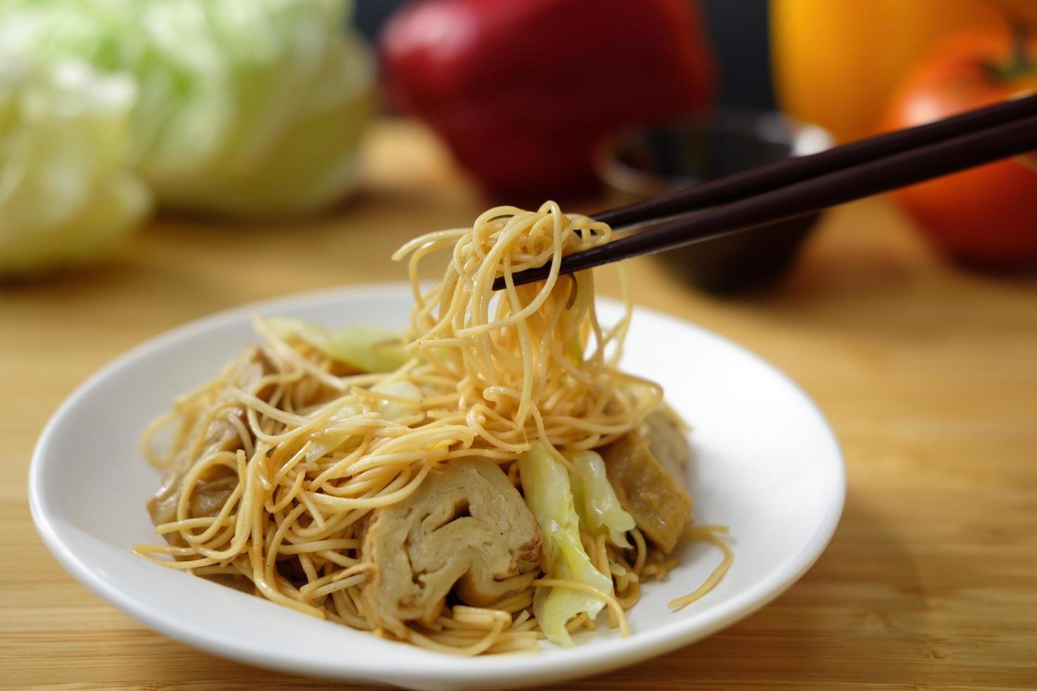Chopsticks holding noodles on plate photo