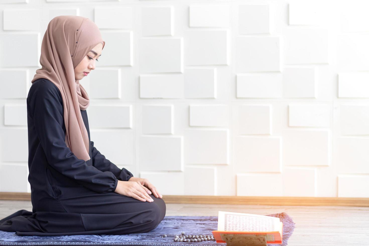 mujeres musulmanas vestidas con hijab negro, rezando foto