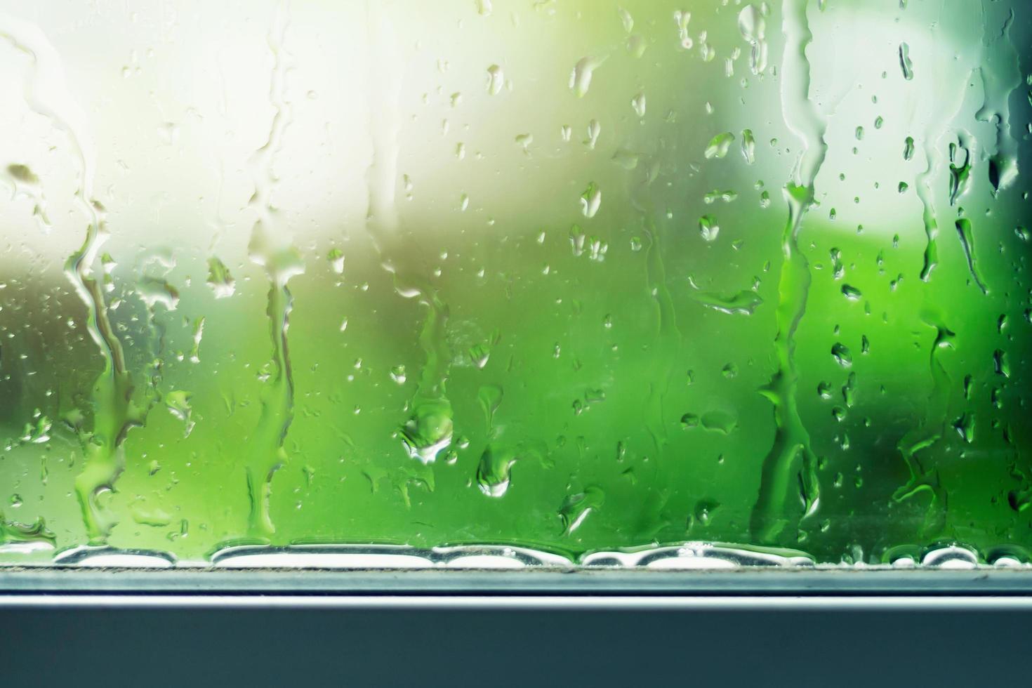 gotas de agua bajando por una ventana de vidrio foto