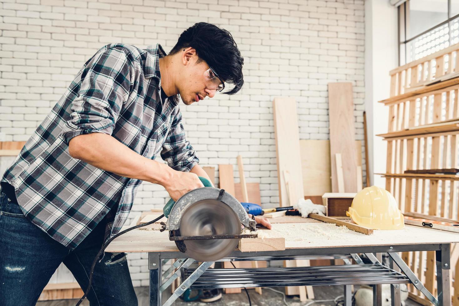 Carpenter cutting timber photo