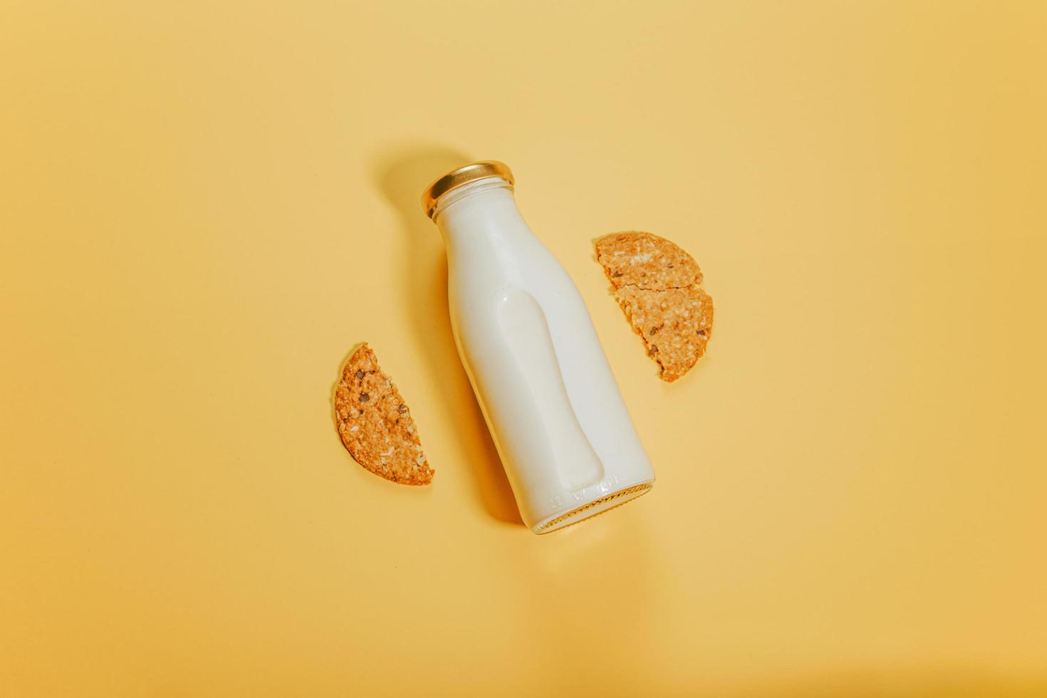 botella de leche entre dos mitades de una galleta foto