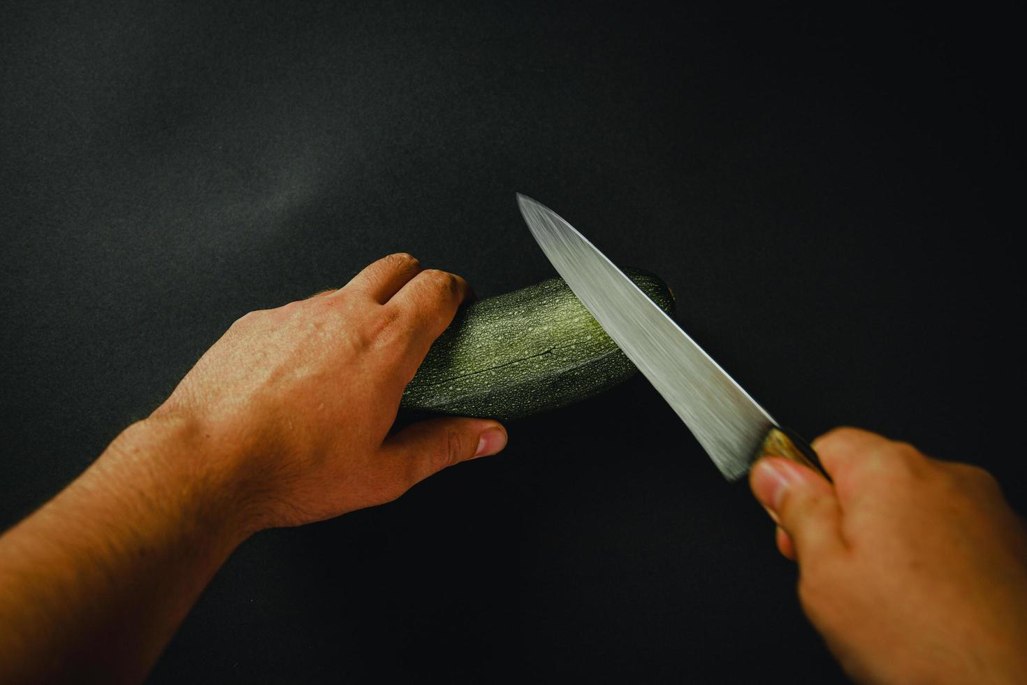 Two hands and knife cutting a cucumber photo
