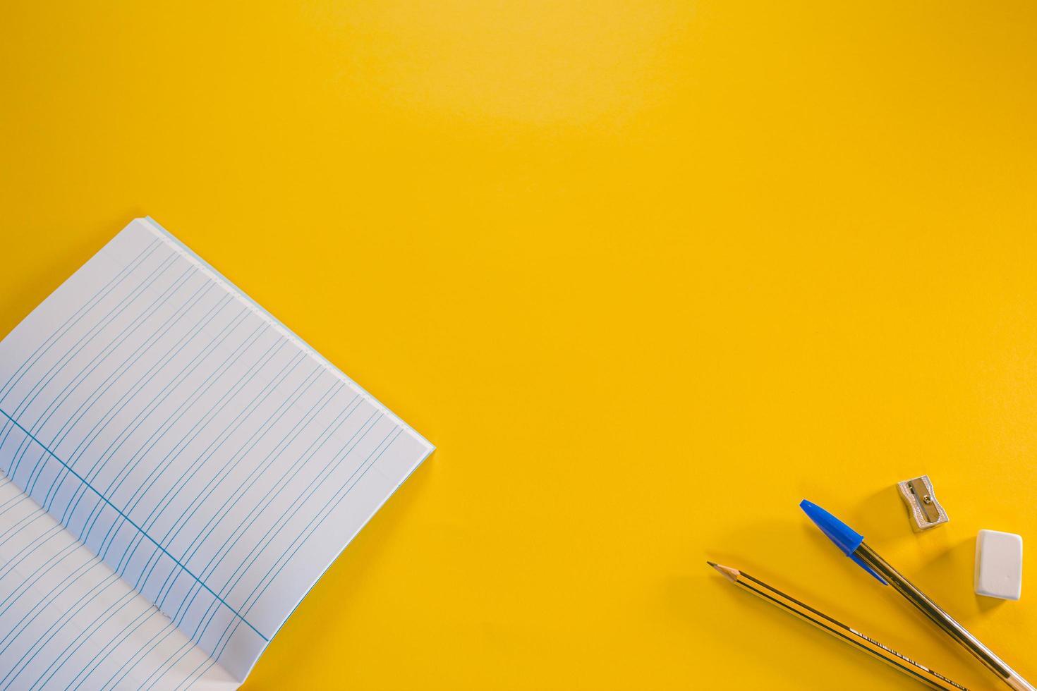 cuaderno, bolígrafo, lápiz, borrador y sacapuntas sobre fondo amarillo foto