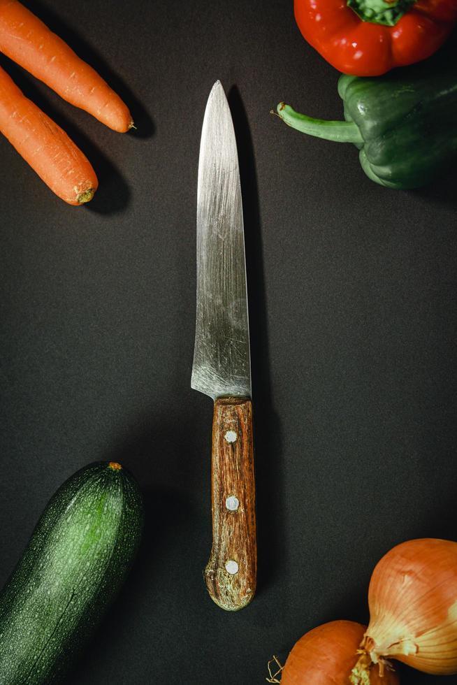 Cuchillo de chef rodeado de verduras sobre fondo oscuro foto