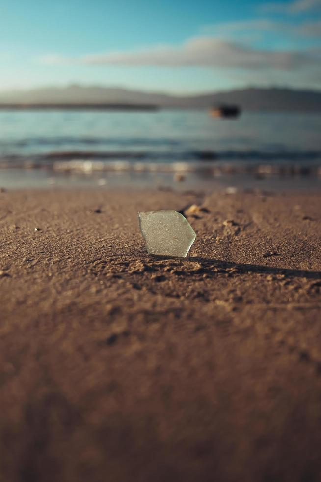 Piece of glass in sand at beach photo
