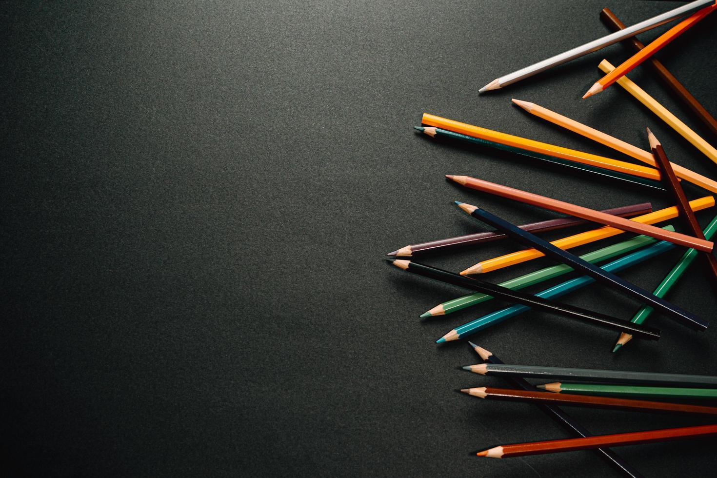 lápices de colores en un lado del fondo oscuro foto