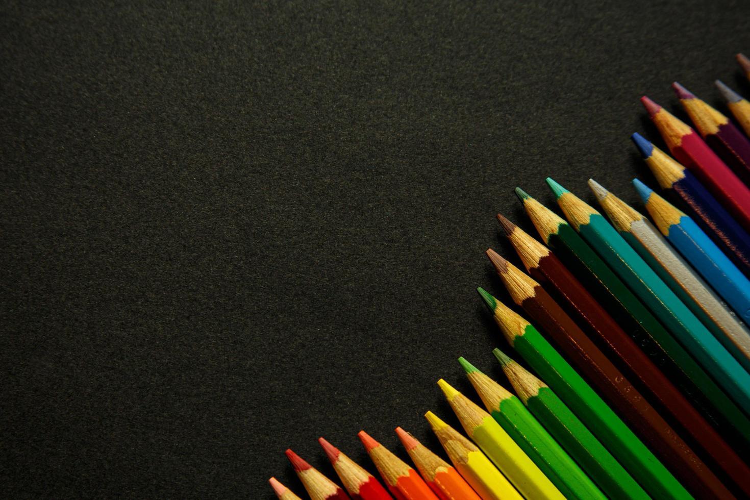 Lápices de colores en fila desigual sobre fondo oscuro foto