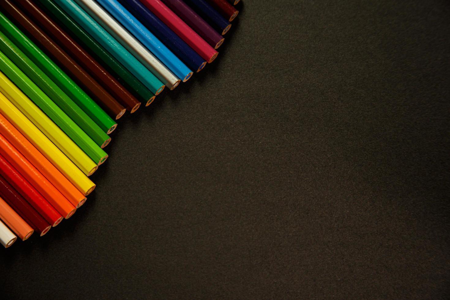 lápices de colores sobre fondo oscuro foto