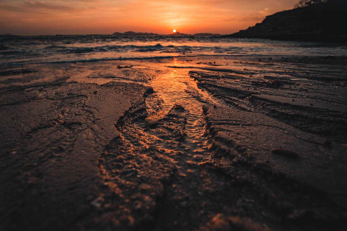 Primer plano de la arena en la playa con puesta de sol foto
