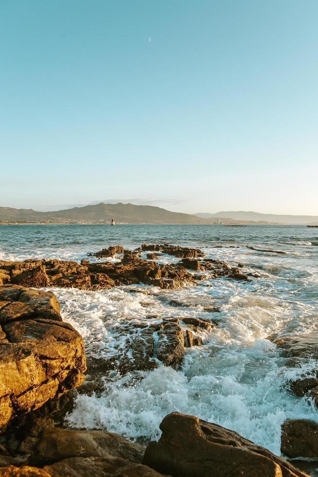 rompiendo el agua en las rocas en una costa foto