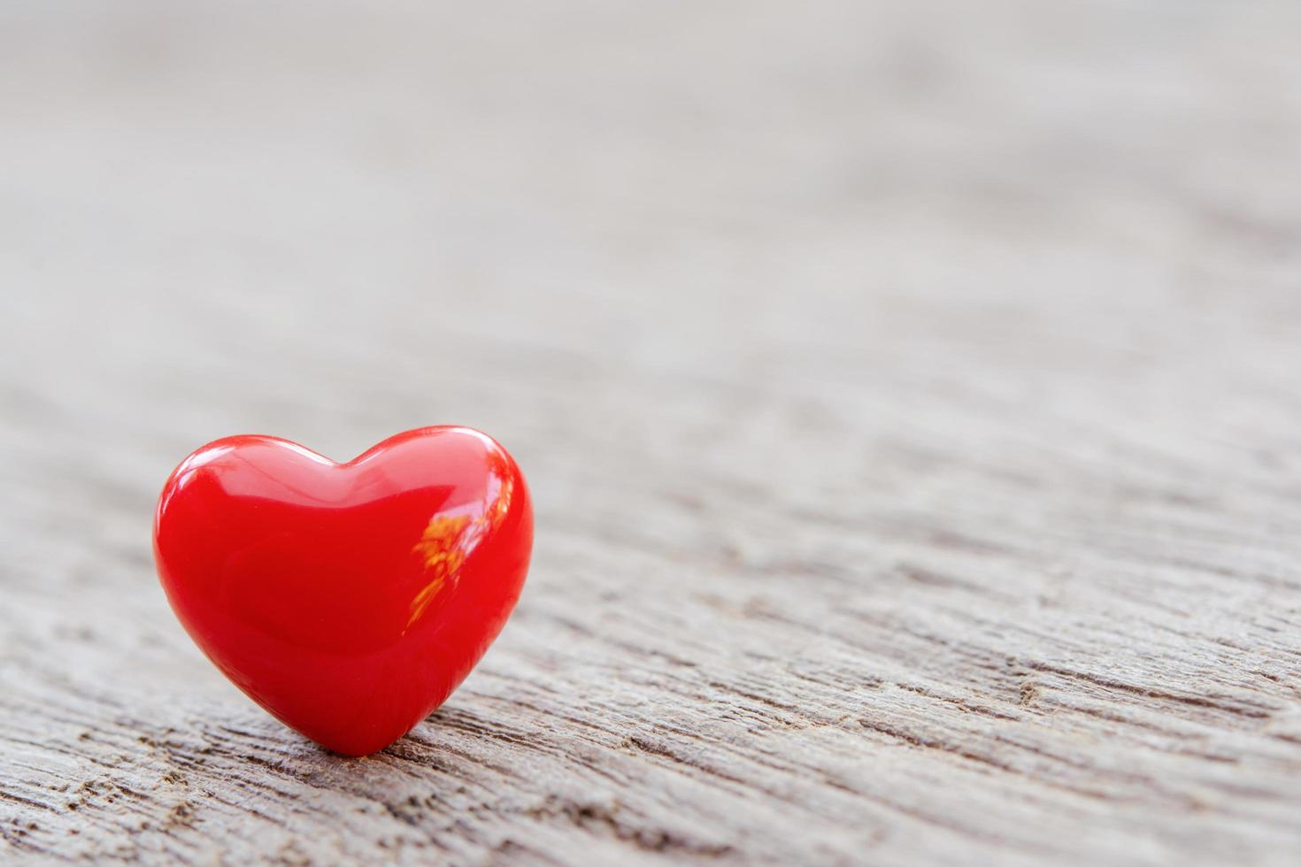 Red heart on wooden plank photo