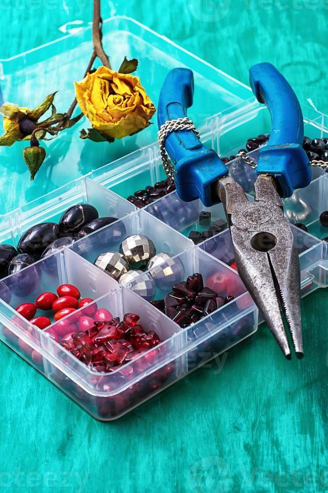 box of beads for needlework on wooden table photo