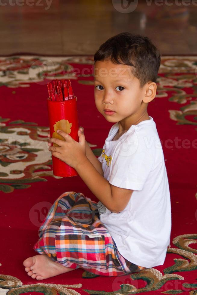Little boy shake bamboo cylinder for fortune tell photo