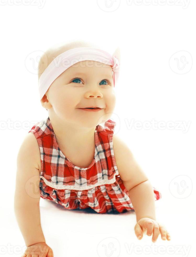 Portrait of little baby girl crawls on a white background photo