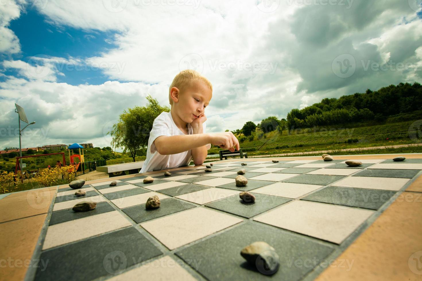 Child playing draughts or checkers board game outdoor photo