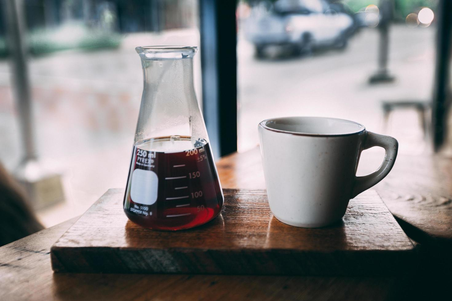 Erlenmeyer flask and white mug on brown wooden table photo