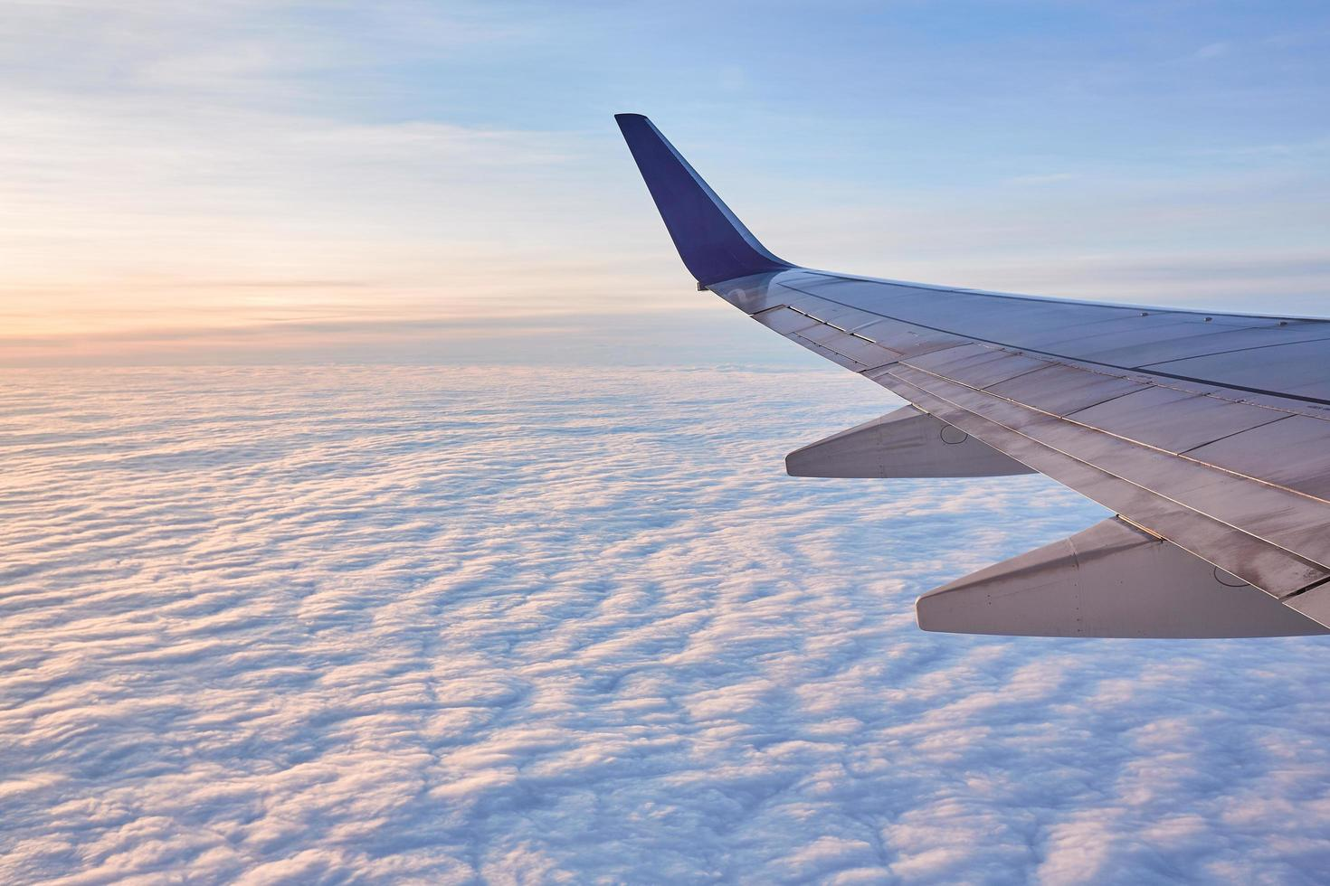 Airplane wing over white clouds photo