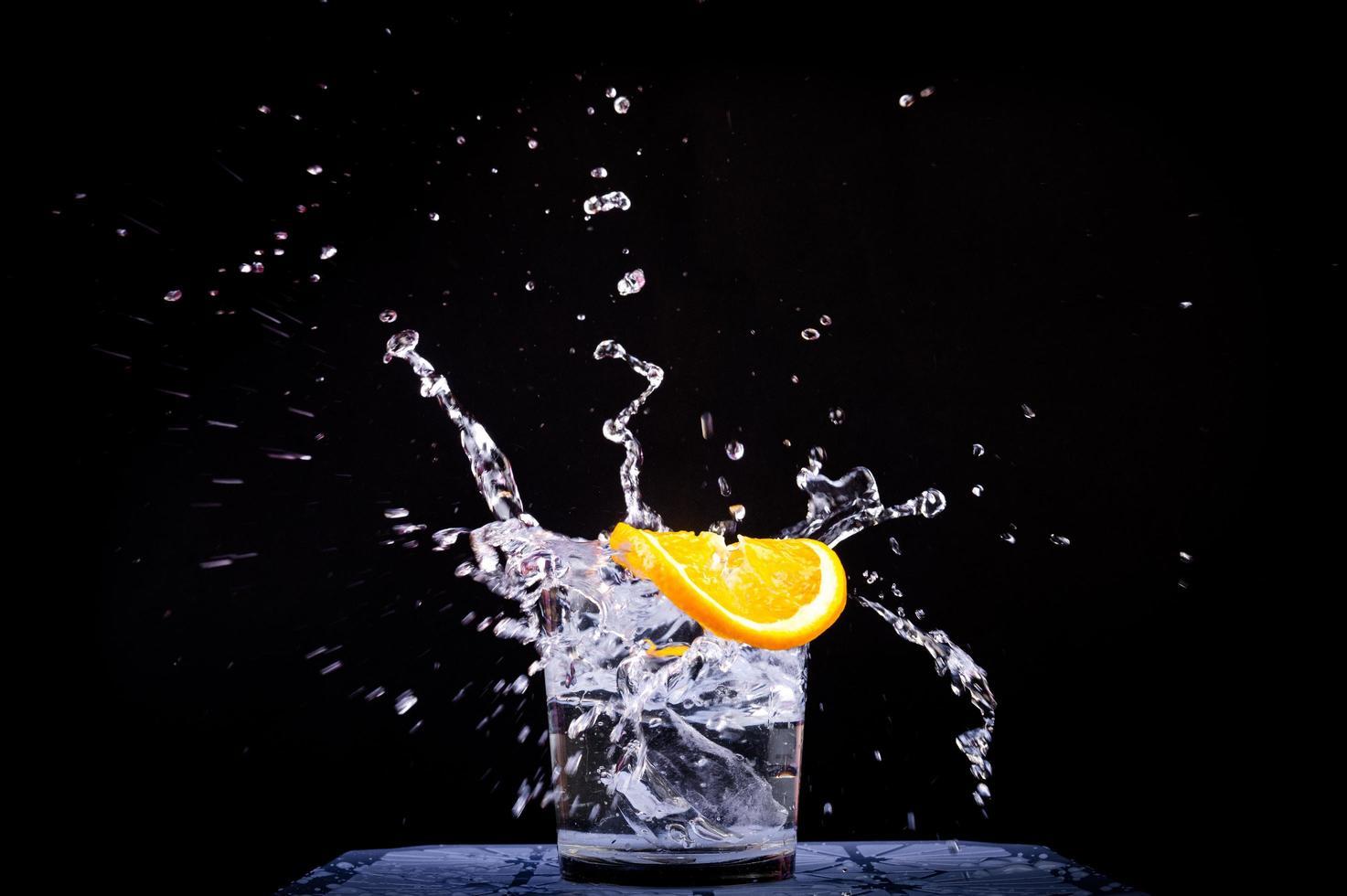 Splash of water in glass with sliced lemon photo