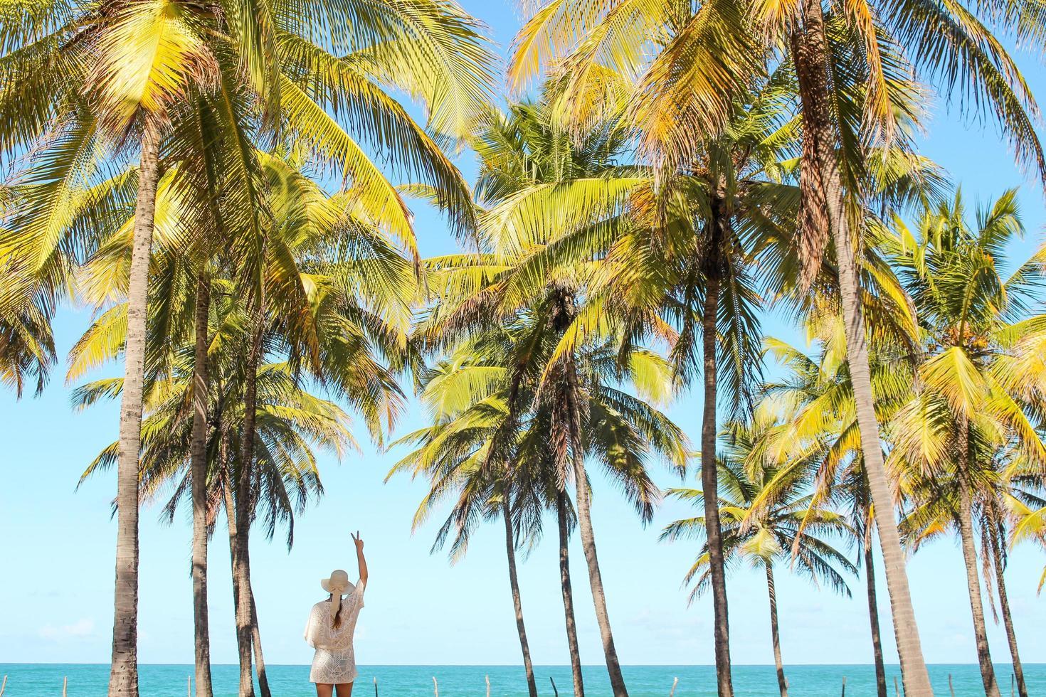 Mujer de pie entre palmeras en la playa foto