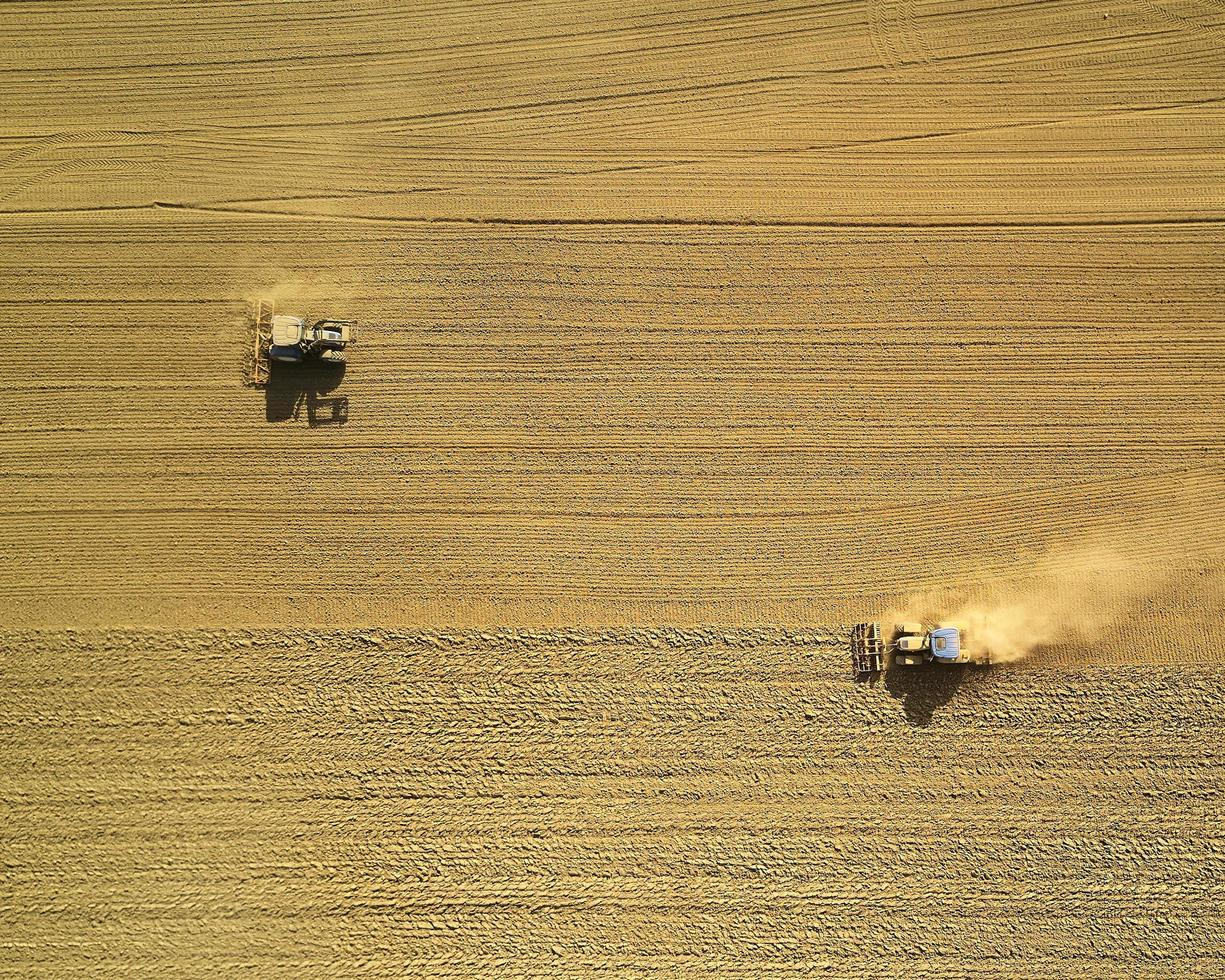 Two harvesters on brown field photo
