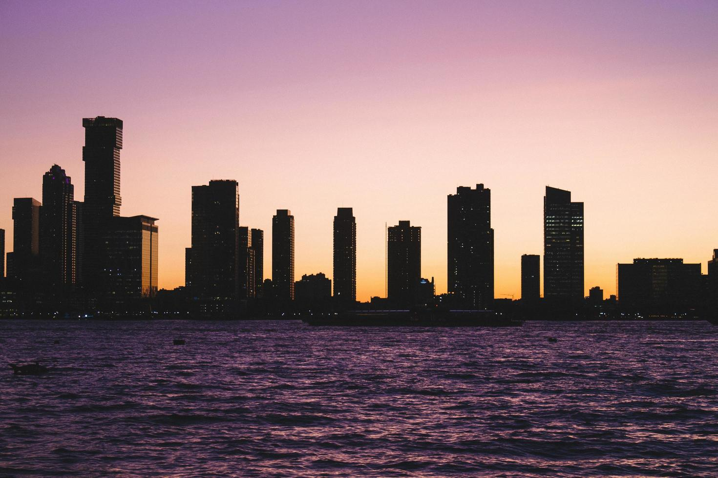 City skyline and water against purple sky photo