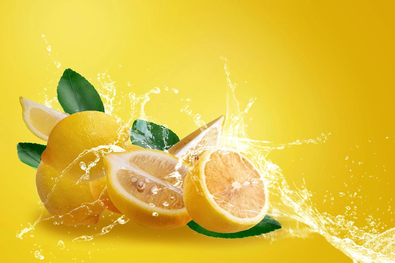 Water splashing on fresh sliced ripe yellow lemons photo