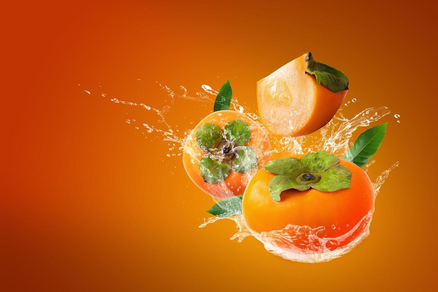 Water splashing on fresh persimmons  photo