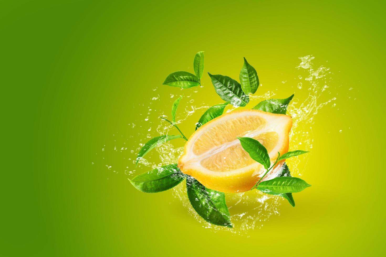 Water splashing on lemons and green tea leaf  photo