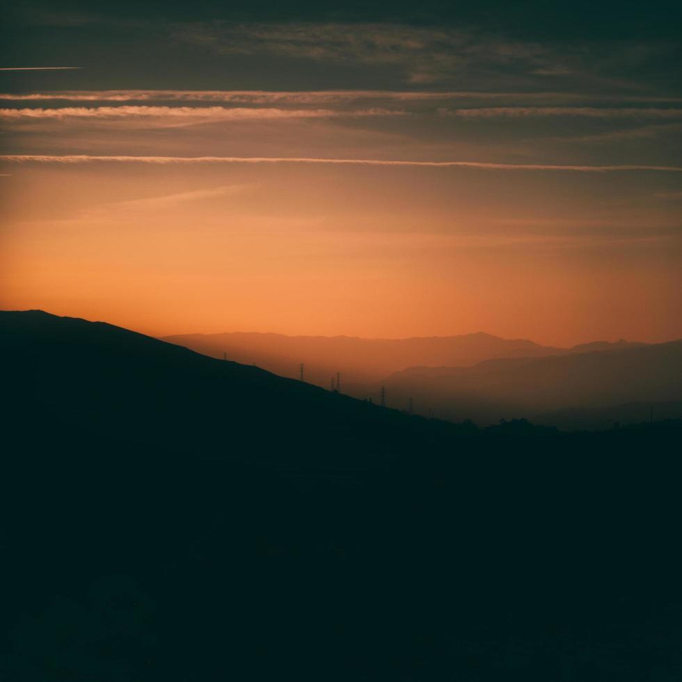 silueta de montañas bajo el cielo naranja foto