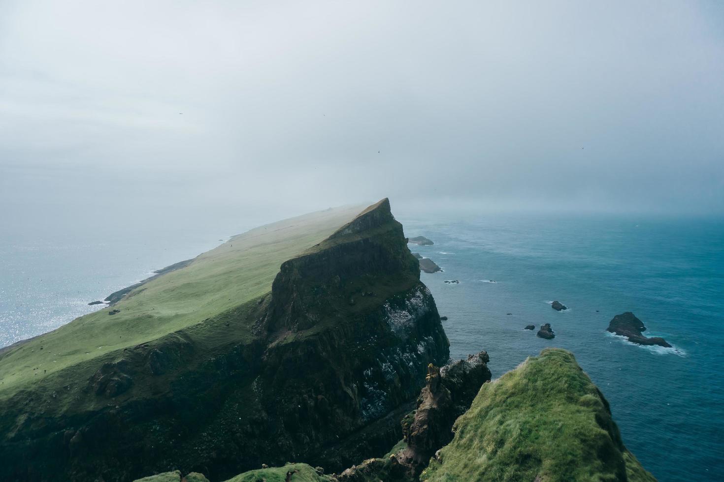 Cliff near ocean under foggy sky photo