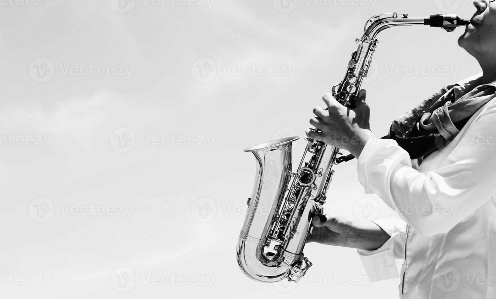 Saxophonist playing on saxophone photo