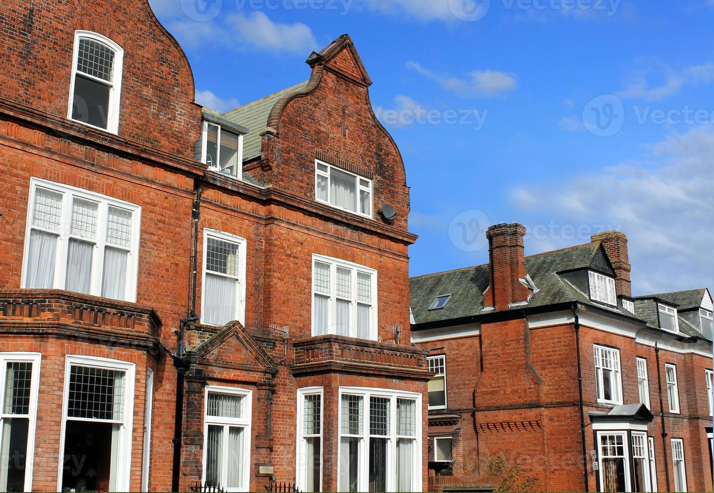 Row of red brick houses in street photo