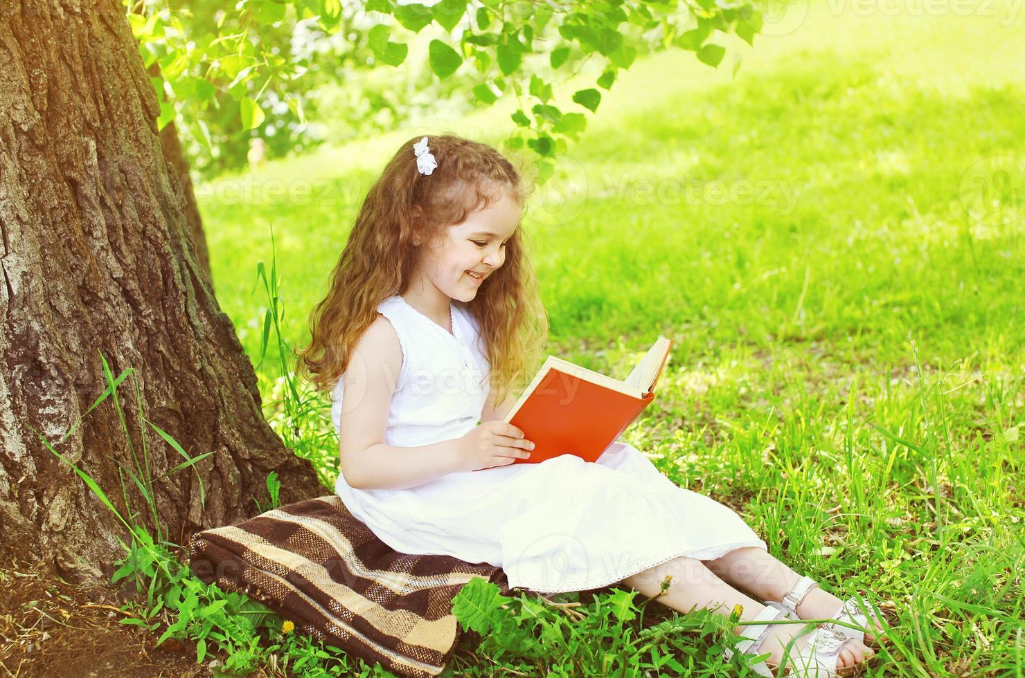 Niña sonriente leyendo un libro sobre el césped cerca del árbol foto