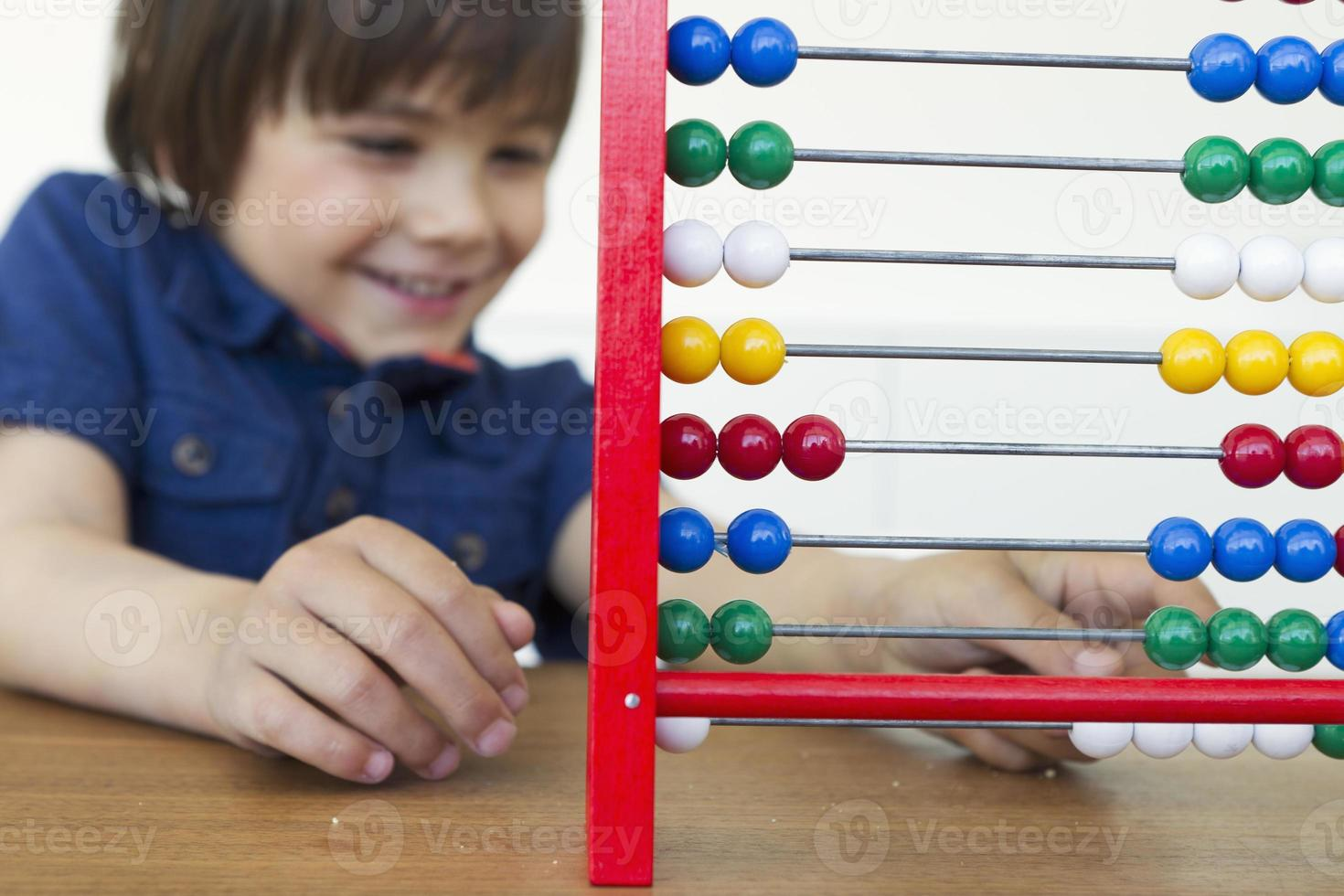 Smiling boy playing with abacus photo